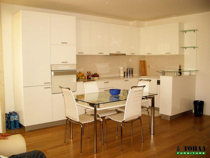 Бяла кухня с бели уреди и стъклена масичка